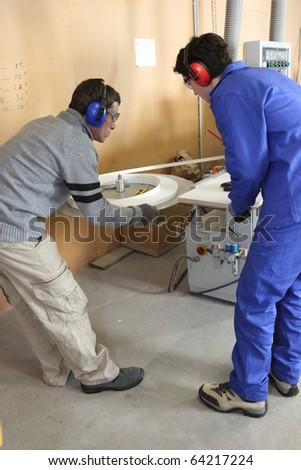Carpenter and apprentice working in studio - stock photo