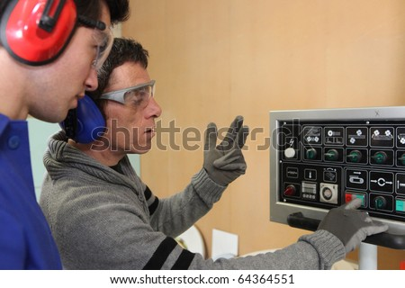 Carpenter and apprentice working in studio - stock photo