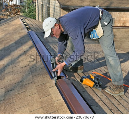 Carpenter applying caulk to ridge vent - stock photo