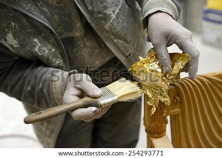 Carpenter Applying Golden Leaf To A Furniture  - stock photo