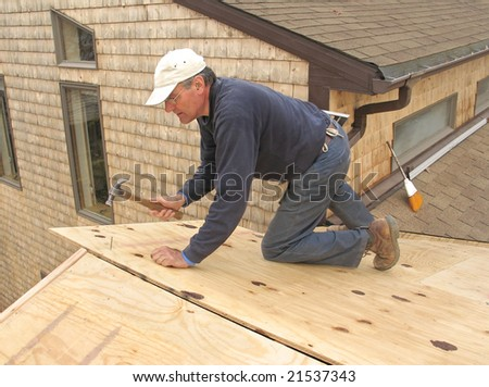 Carpenter applying plywood sheathing to roof of addition - stock photo