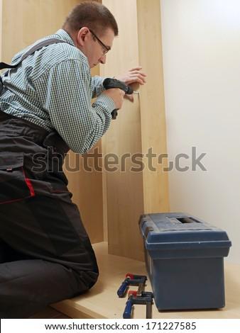 Carpenter assembling wardrobe furniture in walk-in closet - stock photo