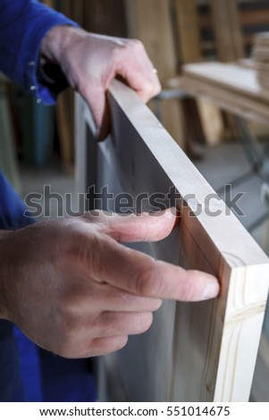 Carpenter at work measuring a distance with his fingers in his workshop.