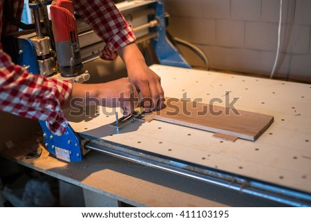 Carpenter attaches board to machine the workpiece surface with CNC, joinery, carpentry shop - stock photo