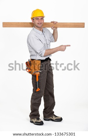 carpenter carrying plank over his shoulder pointing at something