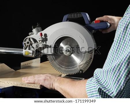 Carpenter cutting flaxboard using sliding compound mitre saw - stock photo