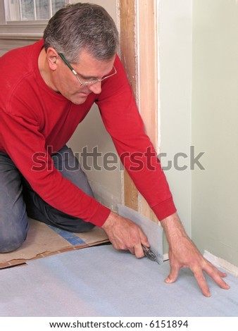 Carpenter cutting underlayment for flooring - stock photo