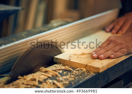 Carpenter cutting wooden board at his workshop