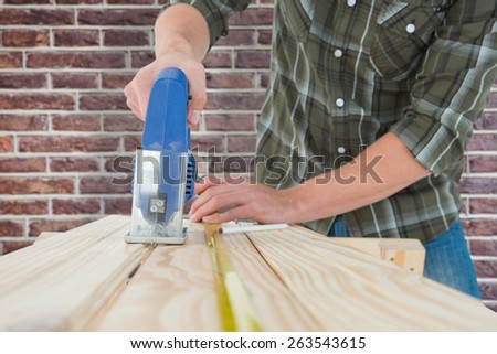 Carpenter cutting wooden plank with electric saw against red brick wall