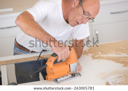 Carpenter drilling into a wooden surface - stock photo