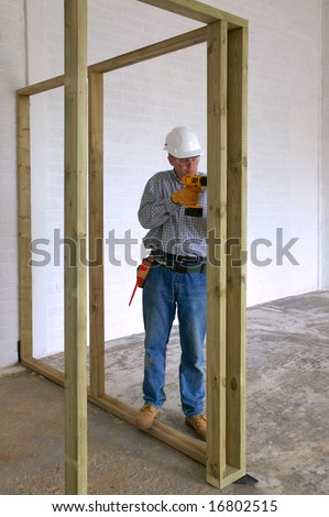 Carpenter drilling into some timber framework in a new house build. - stock photo