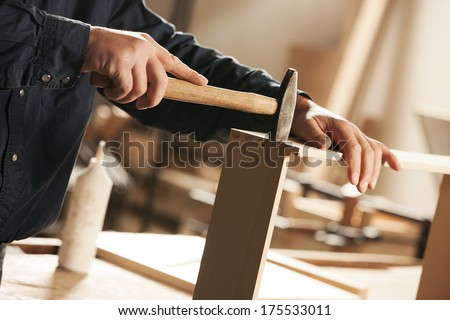 Carpenter hammering a piece of furniture for assembly. - stock photo