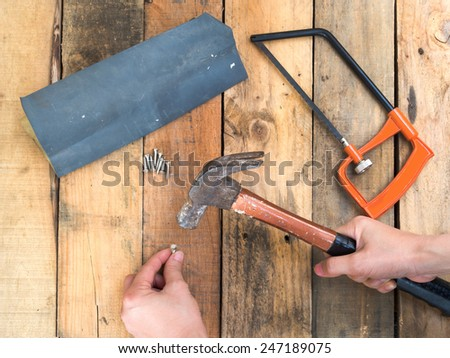 carpenter hand hammering a nail  - stock photo