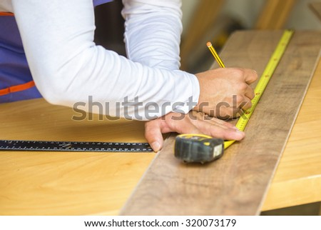 Carpenter hands in the foreground with measuring meter