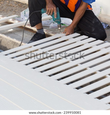 carpenter hands using electric drill on wood at construction site - stock photo