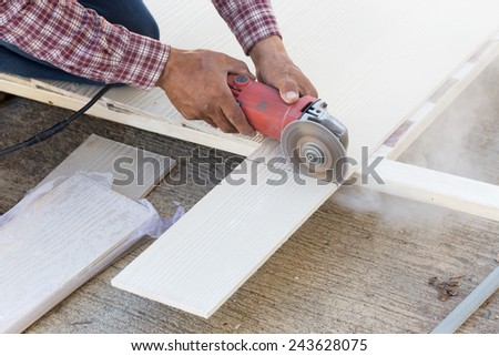 carpenter hands using electric saw on wood at construction site - stock photo