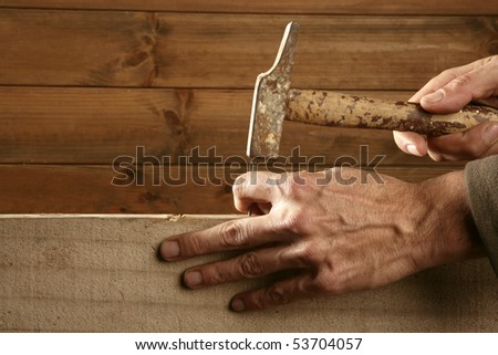 Carpenter hands with hammer wood and nail on wooden background
