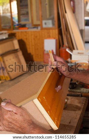 Carpenter hands working at a wooden drawer - stock photo