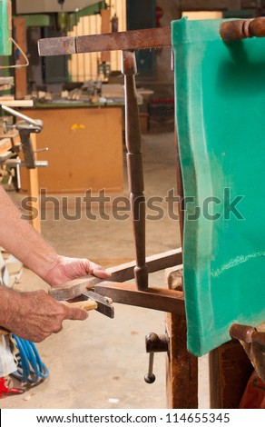 Carpenter hands working at restoring an old chair - stock photo