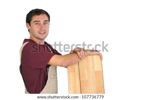 Carpenter holding planks of wood - stock photo