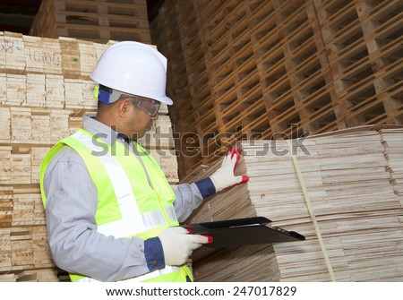 Carpenter in a hard hat standing in front of factory holding a clipboard - stock photo