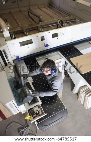 Carpenter in front of a cutting machine - stock photo