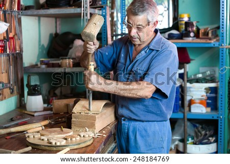 carpenter in the workshop garage handling a chisel and a hammer on a piece of wood / workshop where the cabinetmaker carving wood - stock photo
