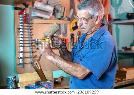 carpenter in the workshop handling a chisel and a hammer on a piece of wood