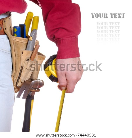 Carpenter in tool belt closeup holds measure tape over white background - stock photo