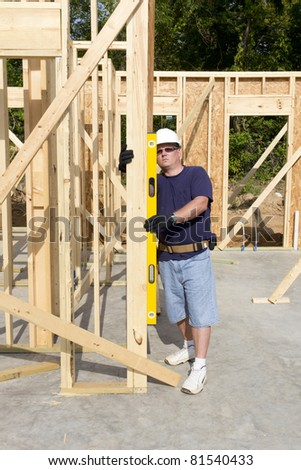 Carpenter inspecting walls for plumb, walls need to be very straight for door casing and windows - stock photo
