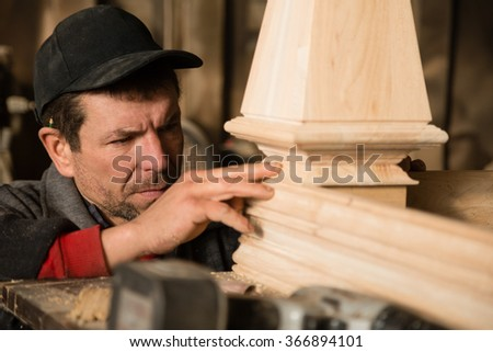 Carpenter inspects to make furniture in the carpentry workshop - stock photo
