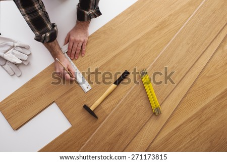 Carpenter installing a wooden flooring and measuring with a precision ruler, top view - stock photo