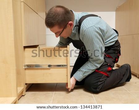 Carpenter installing wardrobe drawers in walk-in closet - stock photo