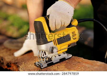 Carpenter is cutting wood with fret saw, outdoor shot, reality shot - stock photo