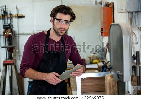 carpenter is posing with his tablet in a dusty workshop