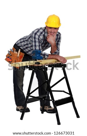 Carpenter leaning on work-bench - stock photo
