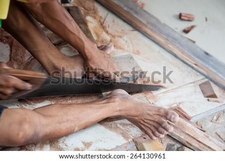carpenter man cut the wood by saw - stock photo