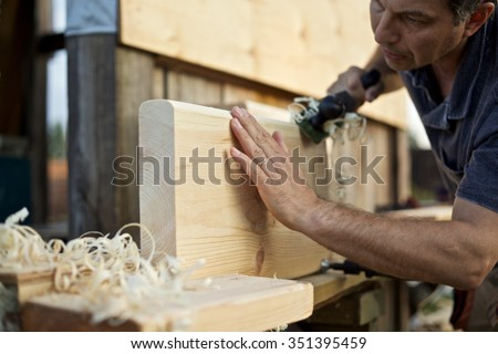 Carpenter manufactures stair treads/Steps to a Wooden Ladder - stock photo
