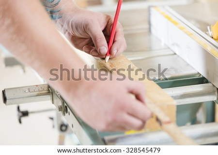Carpenter measures the length of a wood plank before sawing - stock photo