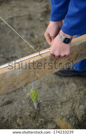 carpenter measures the profile on a building site