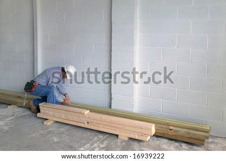 Carpenter measuring a piece of timber - stock photo