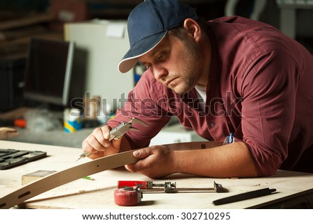 Carpenter measuring chair part with electric callipers in workshop. - stock photo