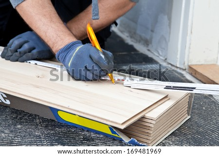 Carpenter measuring new wooden flooring planks using a builders ruler during construction or renovation of a building, close up view of his hands - stock photo