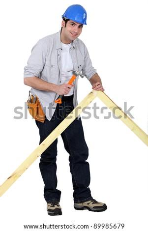 Carpenter nailing a frame - stock photo