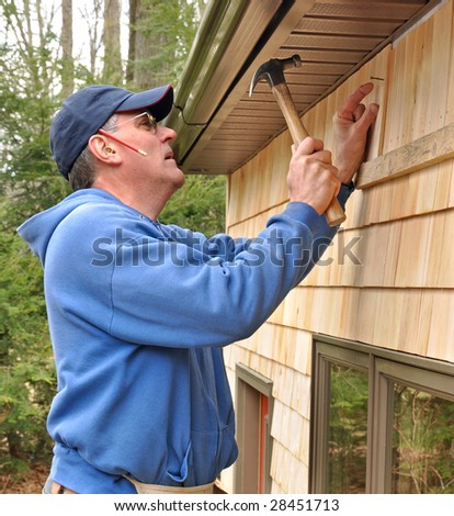 Carpenter nailing cedar shingles to exterior wall - stock photo