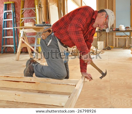 Carpenter nailing interior wall together - stock photo