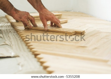 Carpenter on work putting wood parquet pieces. Home construction - stock photo