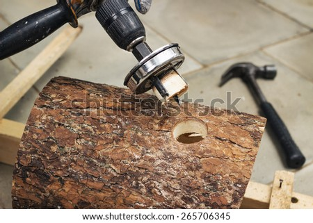 Carpenter performs drill the hole in the wall of the birdhouse - stock photo