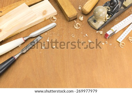 Carpenter plane, chisels, folding rule and wooden planks - stock photo