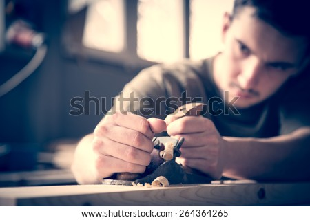 Carpenter planing board in the workshop. - stock photo